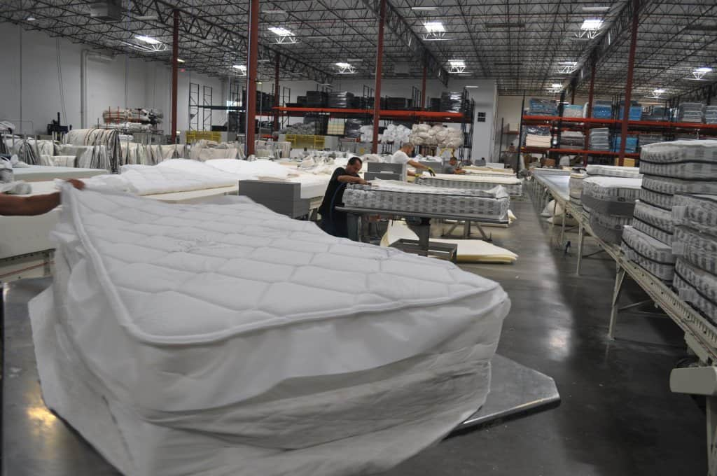 Workers sew the mattress cover to the foam pieces.