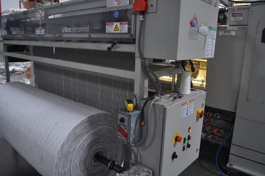 This machine weaves and cuts the side panel pieces for the mattress cover.