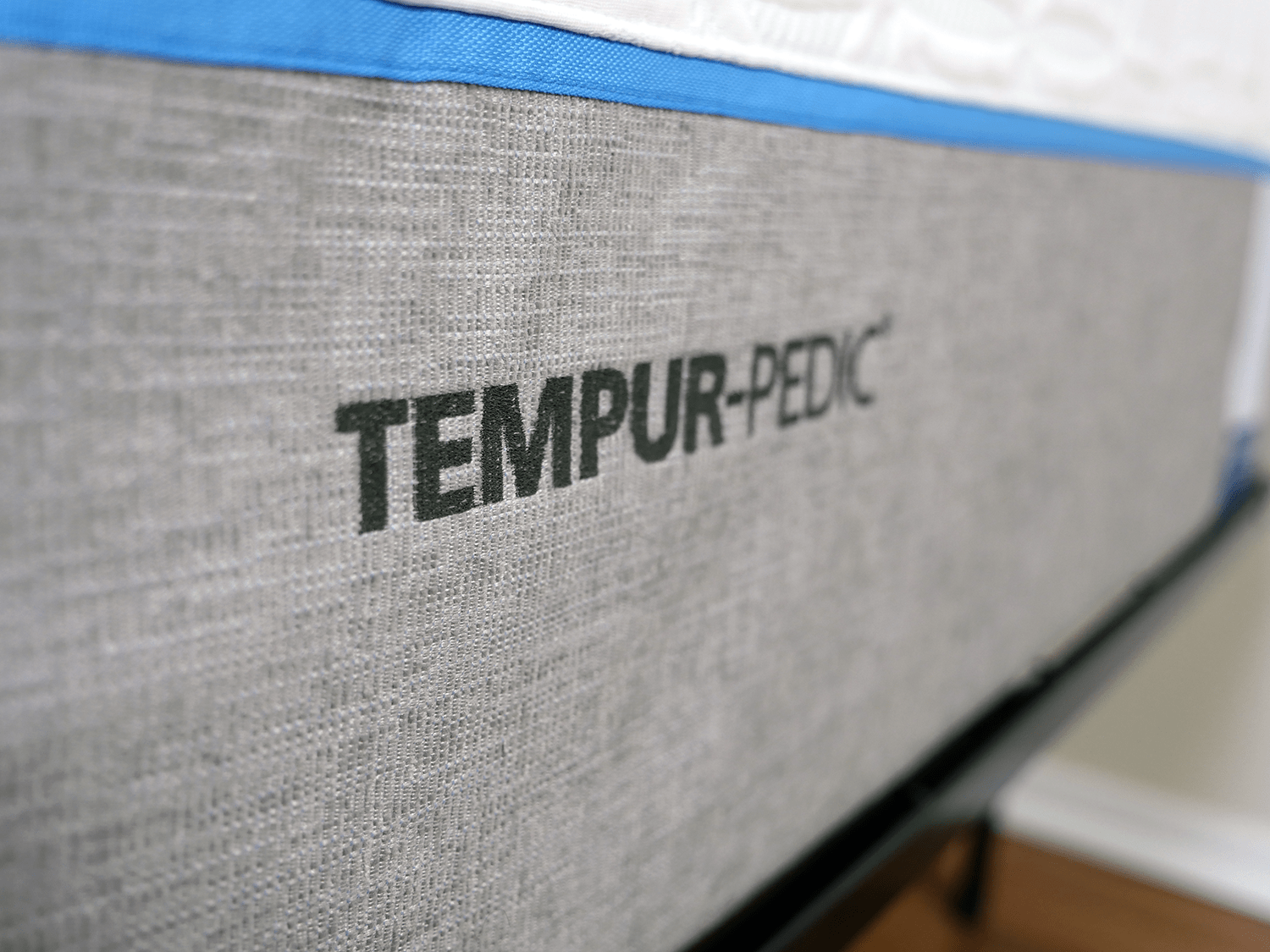 close up shot of the tempurpedic logo embossed to the foot of the mattress