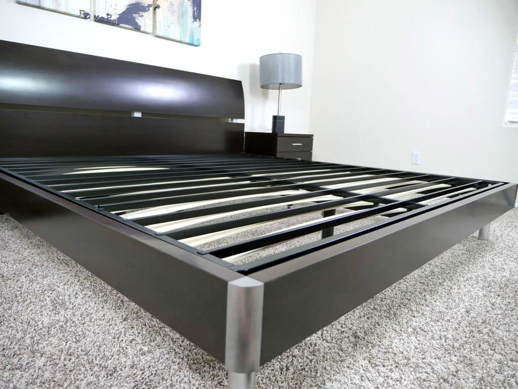 Angled view of the Zinus Bunkie Board sitting on top of an existing platform bed