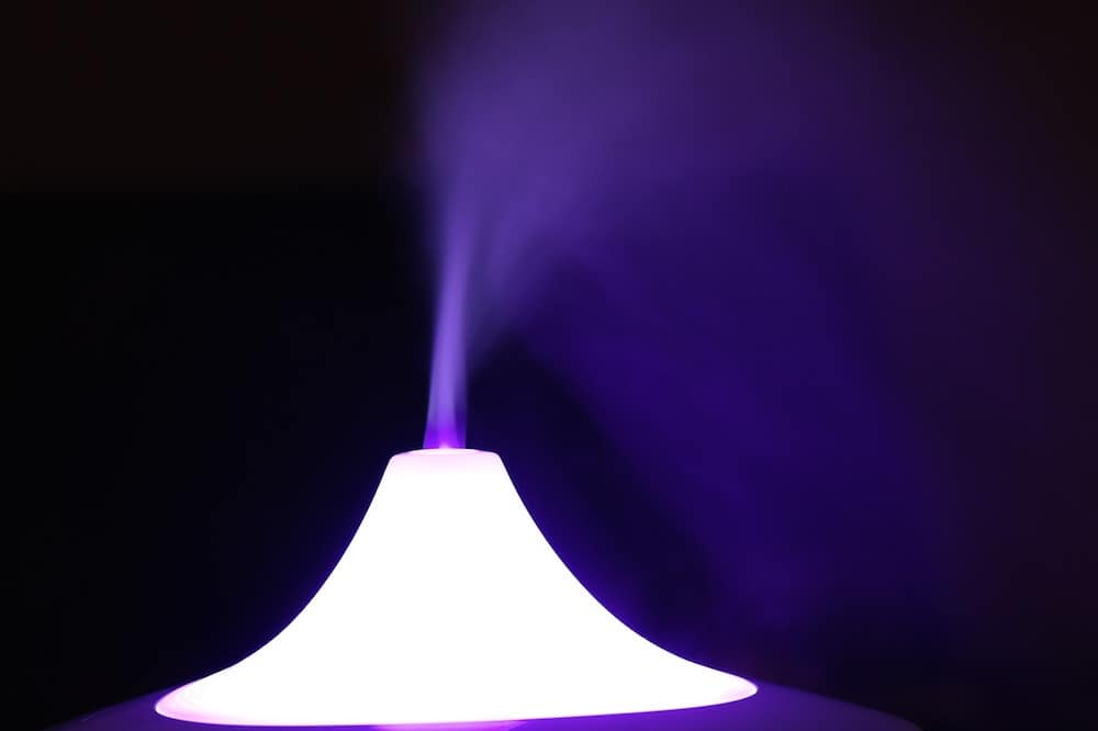 A humidifier blowing moisture into the air, backlit with purple