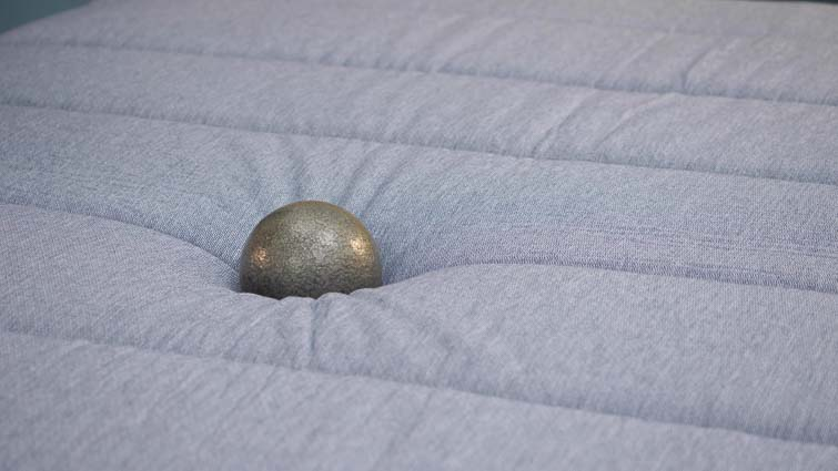 Tuft & Needle Hybrid mattress ball on bed